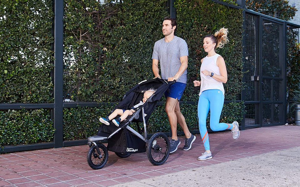 Two adults pushing a child in