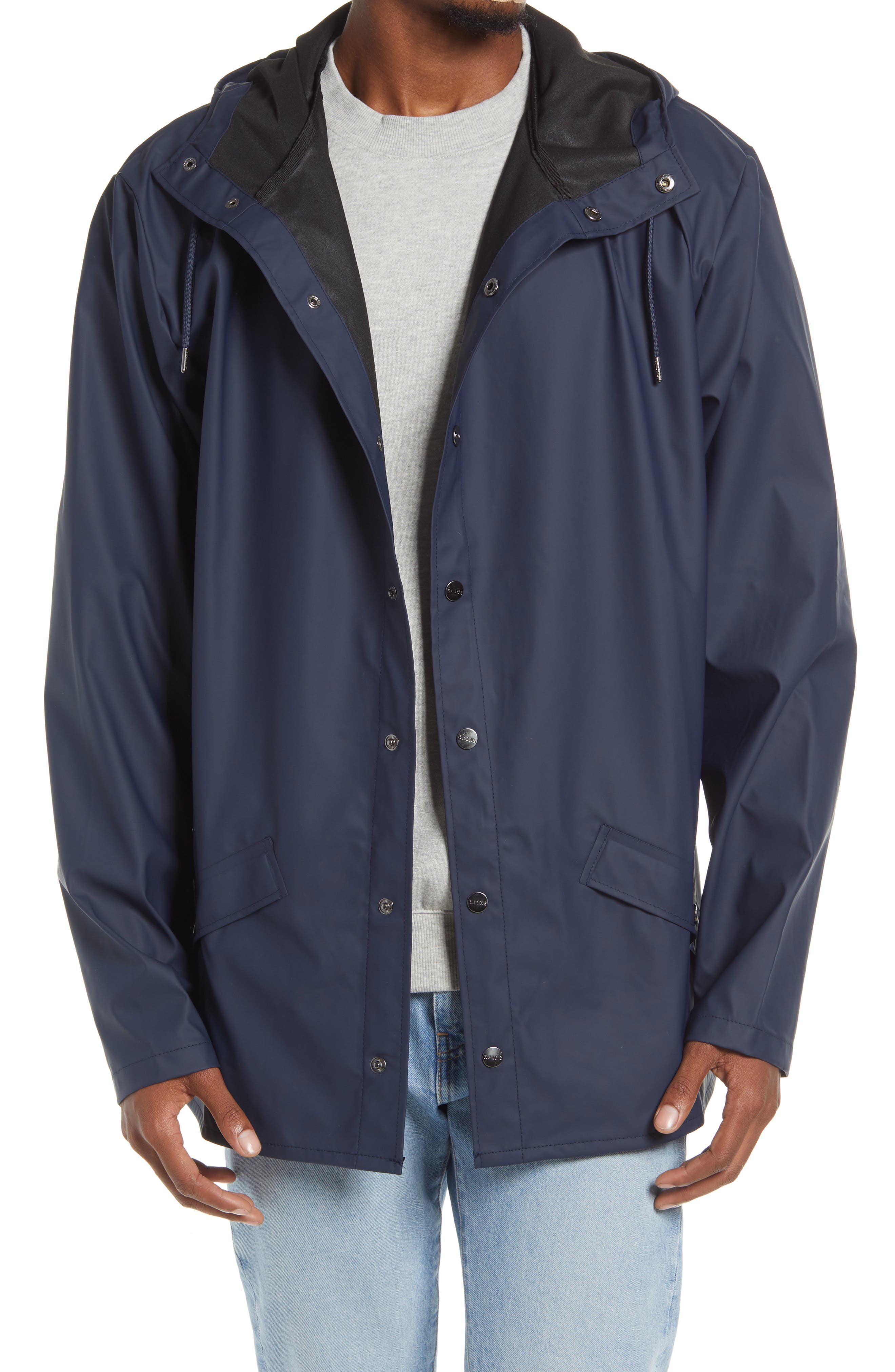 Man wears Rains Lightweight Hooded Rain Jacket