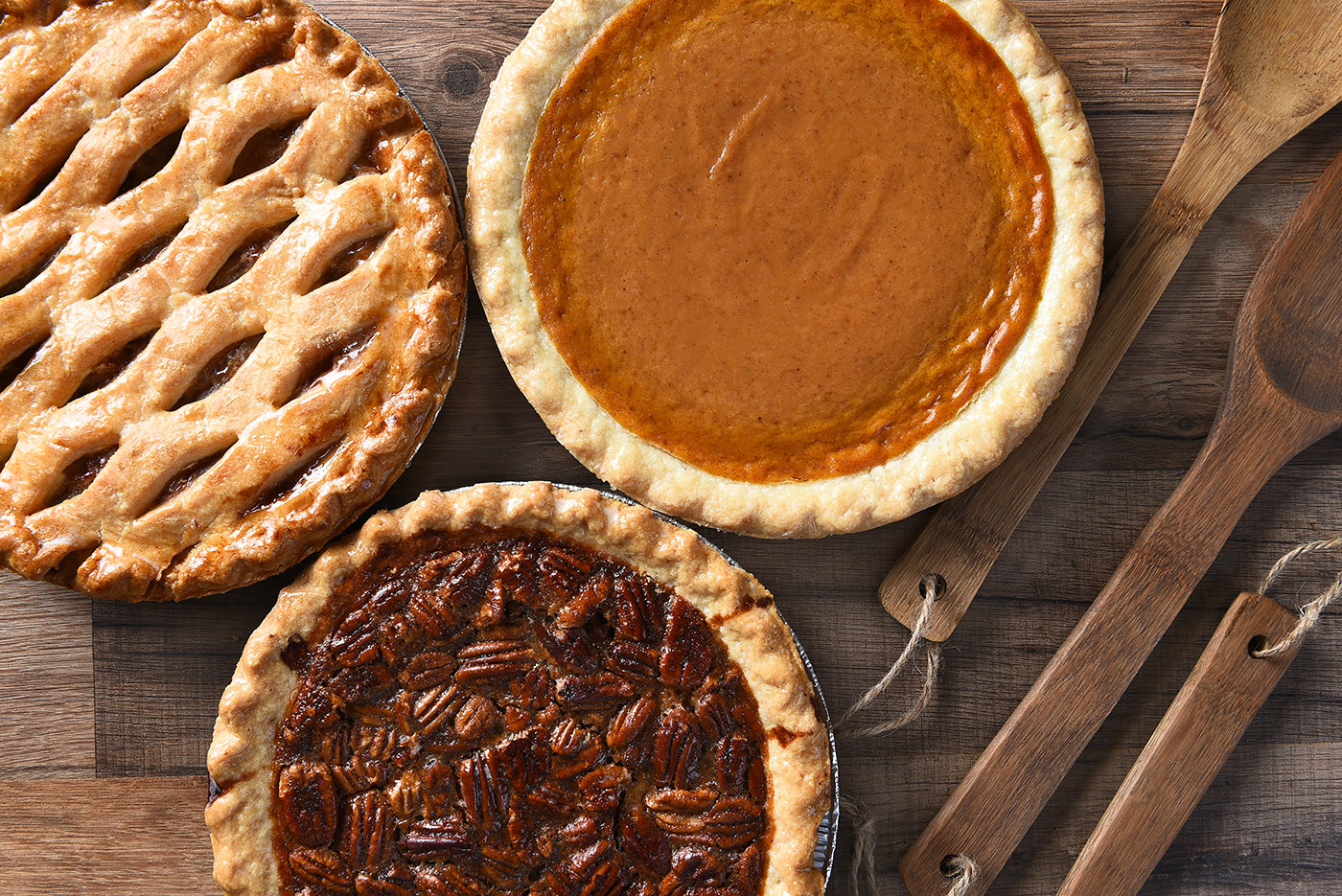 overhead view of three pies, pecan pie, apple pie and pumpkin pie, which is gross