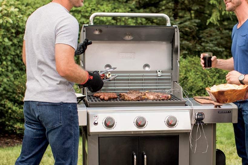 Multiple men grill outside on a