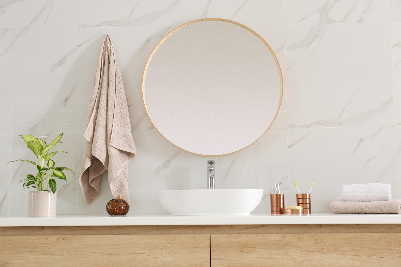 Round mirror over vessel sink in stylish bathroom interior