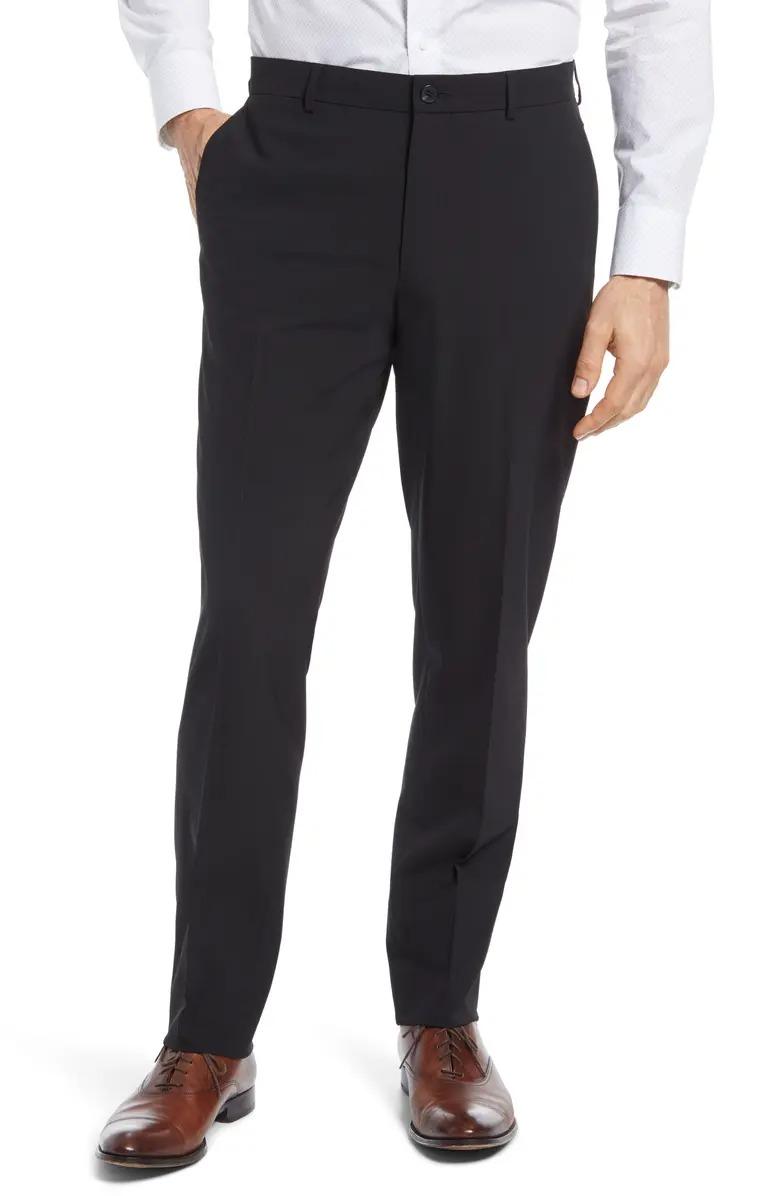 Man wears Nordstrom Tech Smart Trim Fit Strech Dress Pants in black; men's dress pants