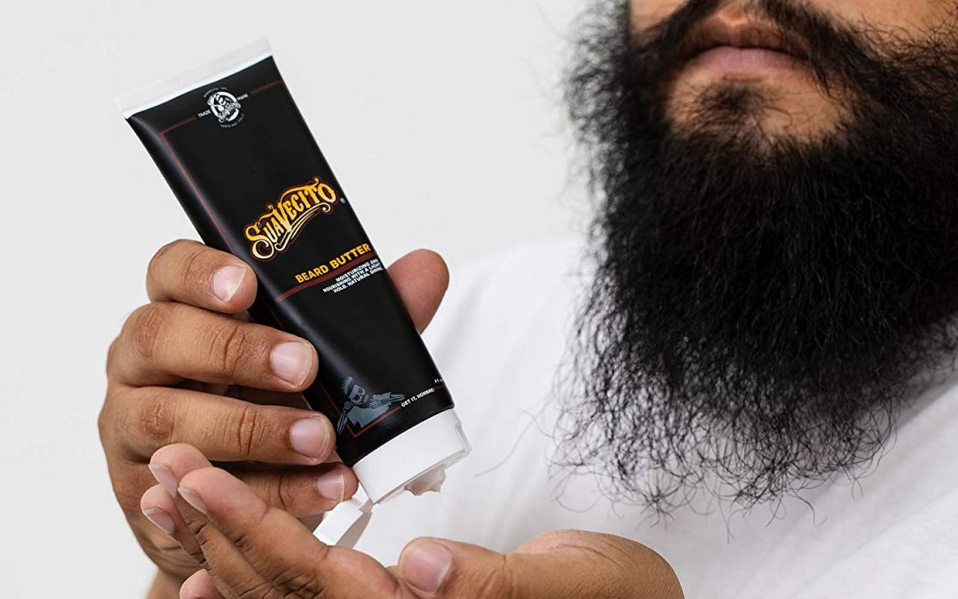 Bearded man squeezes Suavecito Beard Butter