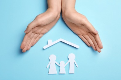 Woman holding hands over paper silhouettes of family and house r