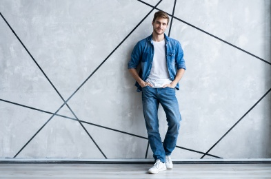 Modern and casual. Full length of handsome young man in jeans shirt looking at camera with smile while standing.