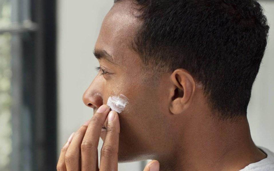 Man applies Lumin skincare product to