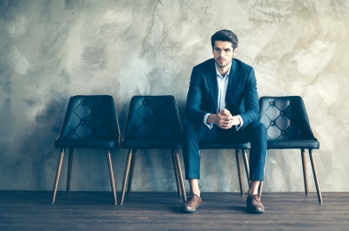 Full length photo of serious worried collar sit on black chair wait for meeting feel nervous wear modern tux tuxedo isolated over grey color background