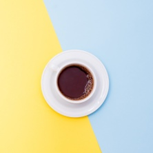 A cup of coffee on yellow and blue background with a copy space