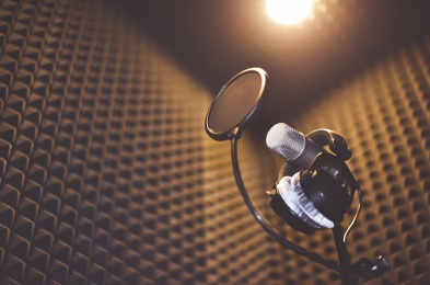Set for professional sound records include microphone with screen, stand, headphones for monitoring and soundproofed room.