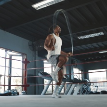 Man With Jumping Rope On Boxing Ring. Asian Male Bodybuilder Using Gym Equipment For Workout. Cardio Exercise For Strong, Healthy Muscular Body. Sexy Guy Training At Sport Center.