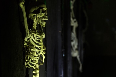 Green lit tortured skeleton hanging on the wall