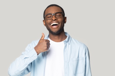 Guy showing thumbs up looking at camera studio shot
